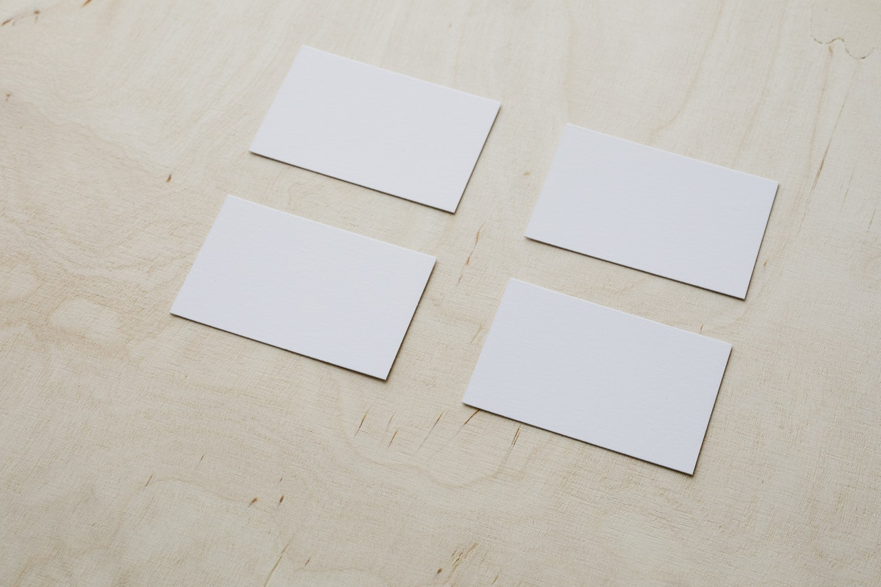 4 Plain Business cards on wooden tabletop